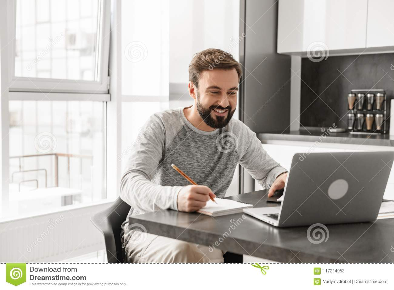 Portrait of a happy young man working on laptop