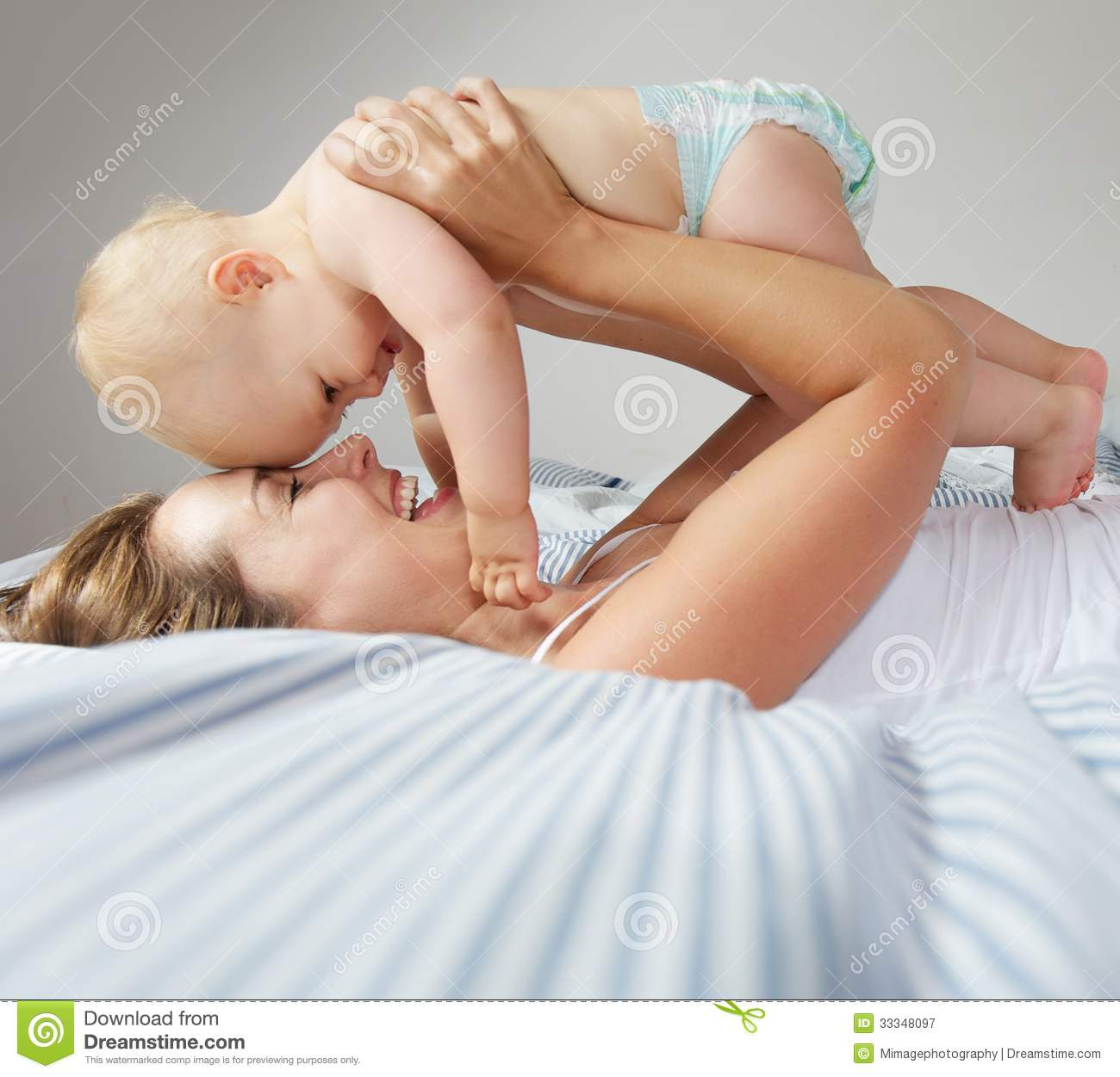 Portrait of happy young mother hugging cute baby