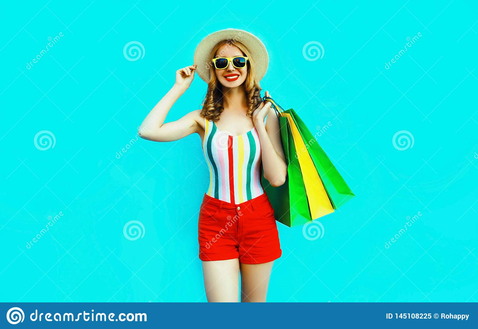 Portrait happy young smiling woman with shopping bags in colorful t-shirt, summer round hat on blue wall