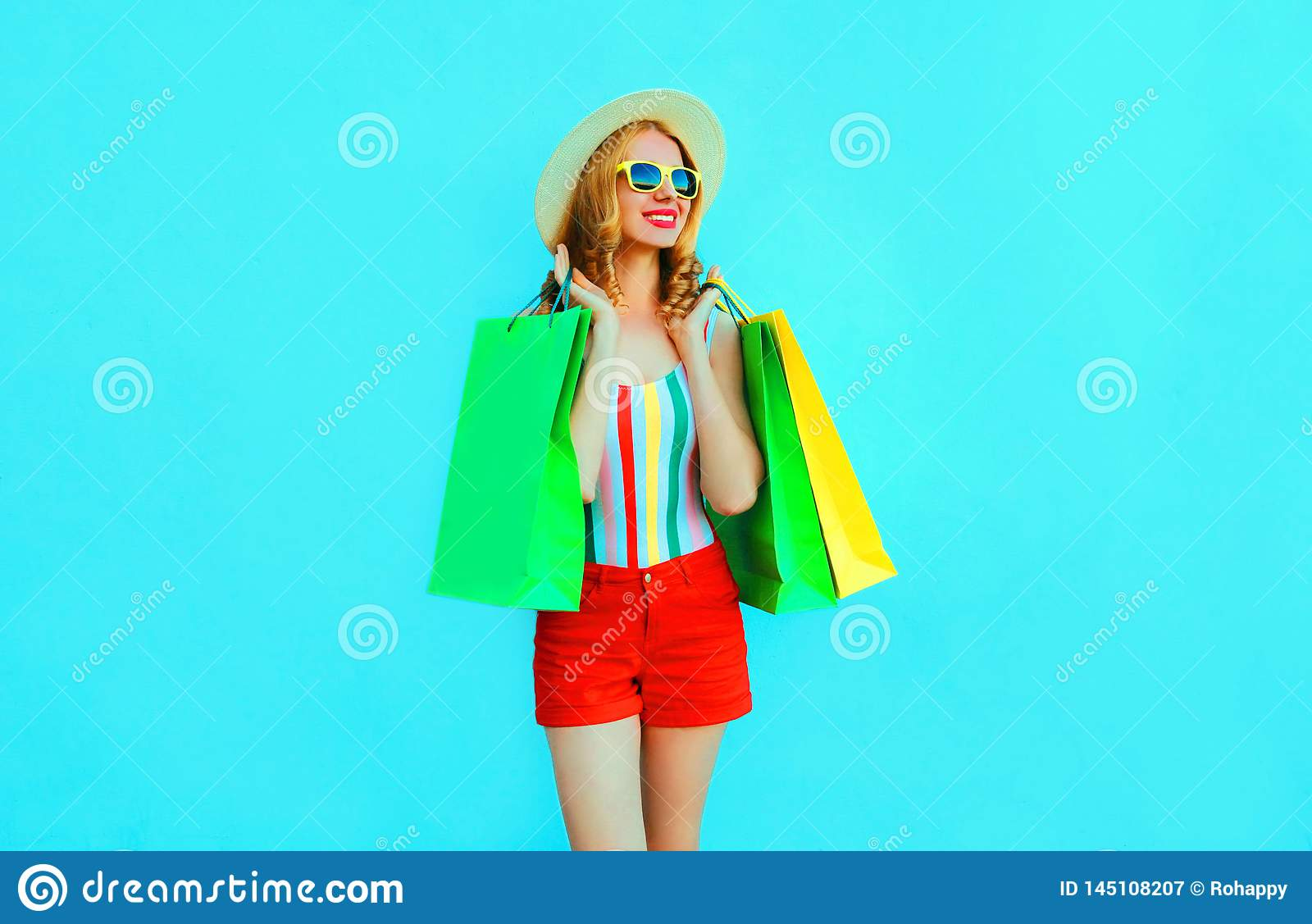 Portrait happy young smiling woman with shopping bags in colorful t-shirt, summer round hat, red shorts on blue wall