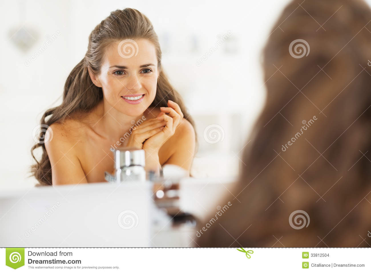 Portrait of happy young woman looking in mirror in for Looking mirror