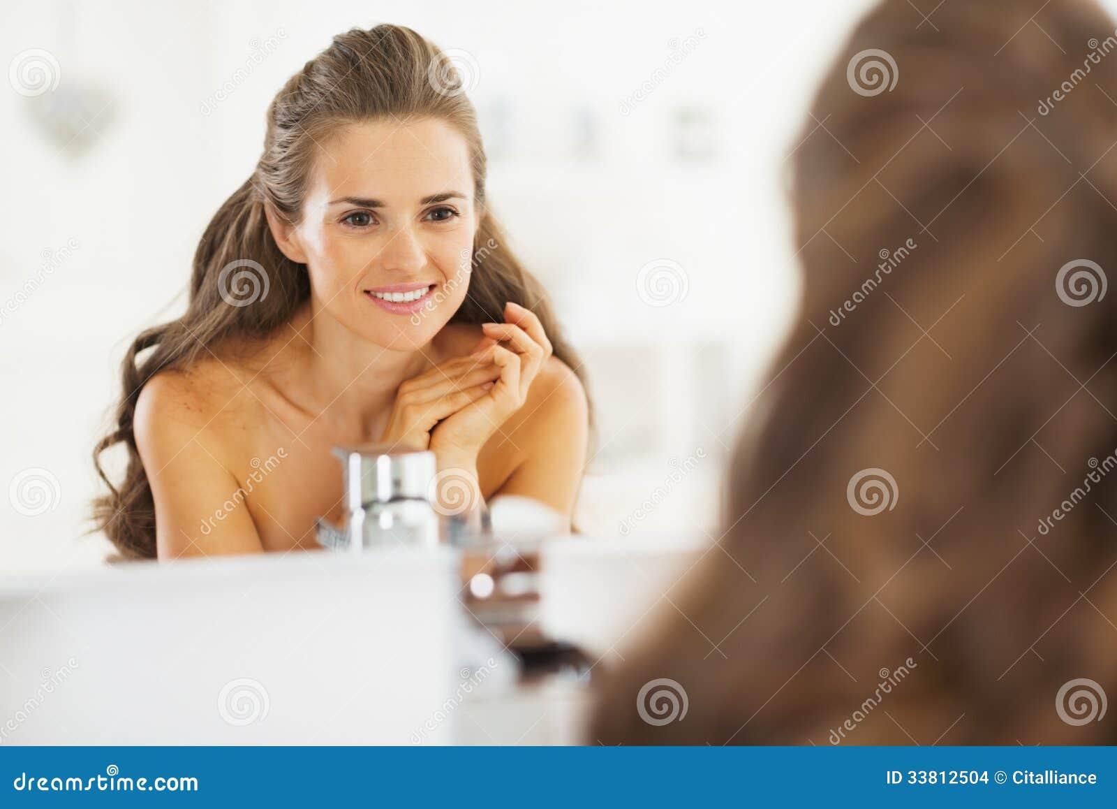 portrait of happy young woman looking in mirror in bathroom stock