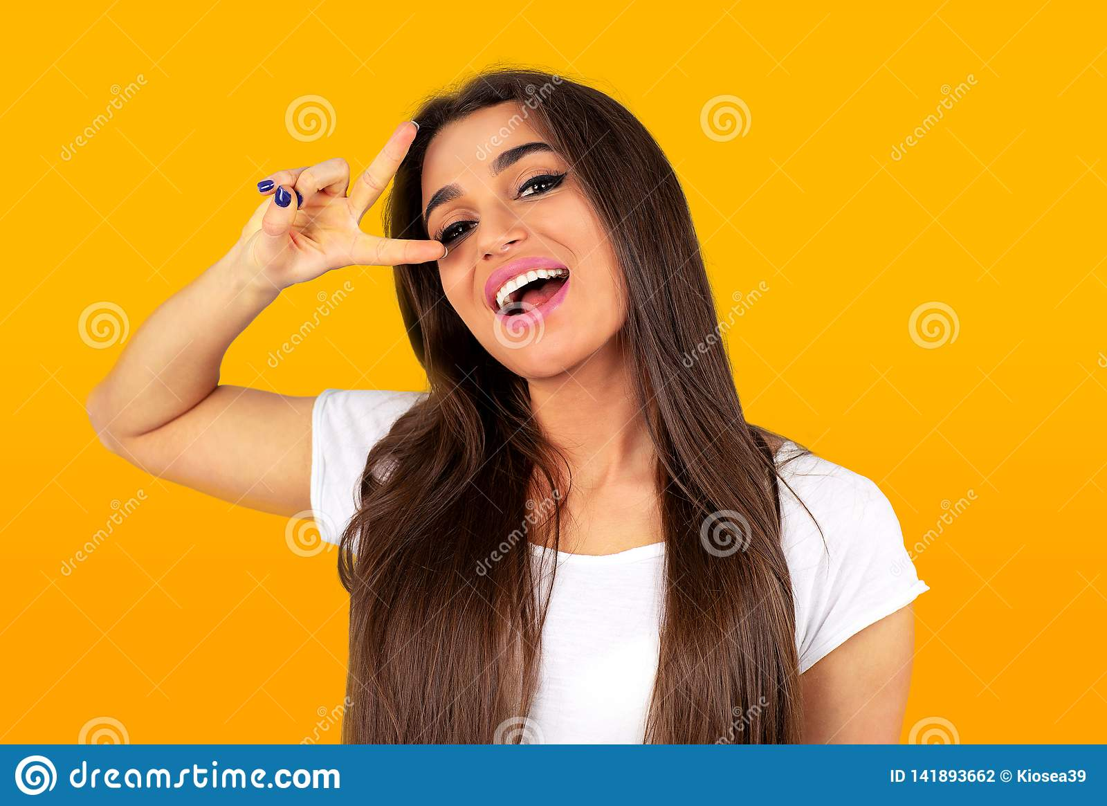 Happy young woman standing showing peace gesture and looking at camera
