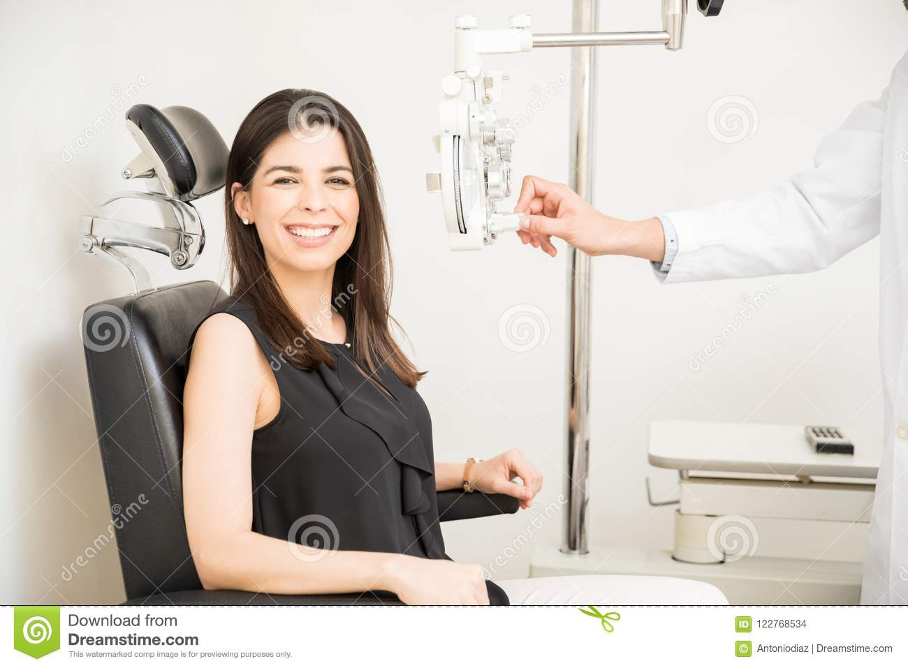 8aea3b6b8bd0 Portrait of happy young women sitting behind phoropter during eye exam while  looking at camera and male doctor hands adjusting panel in clinic