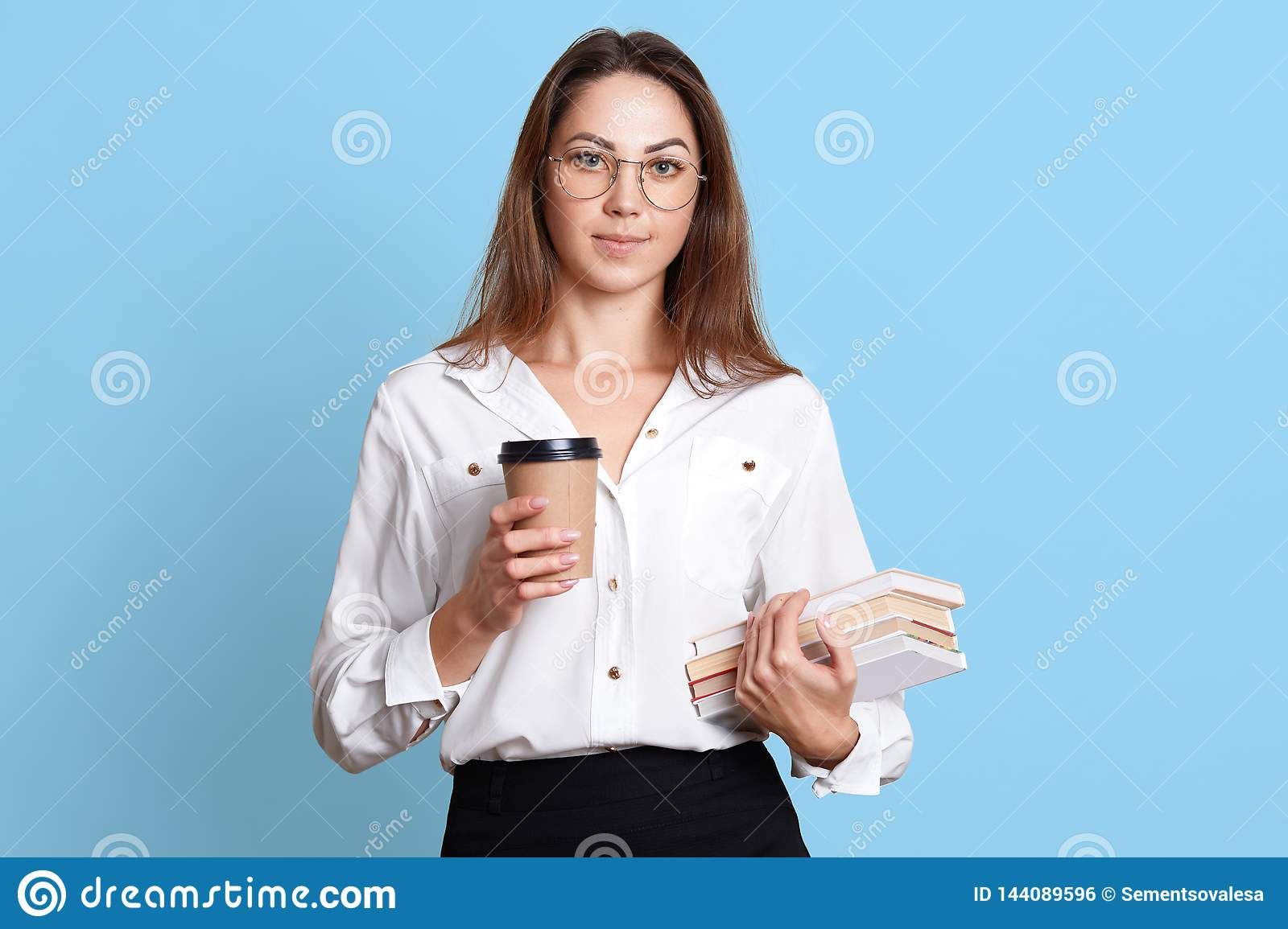 Portrait of hard working serious young lady in trendy glasses, isolated over blue background. European brunette model holds bunch