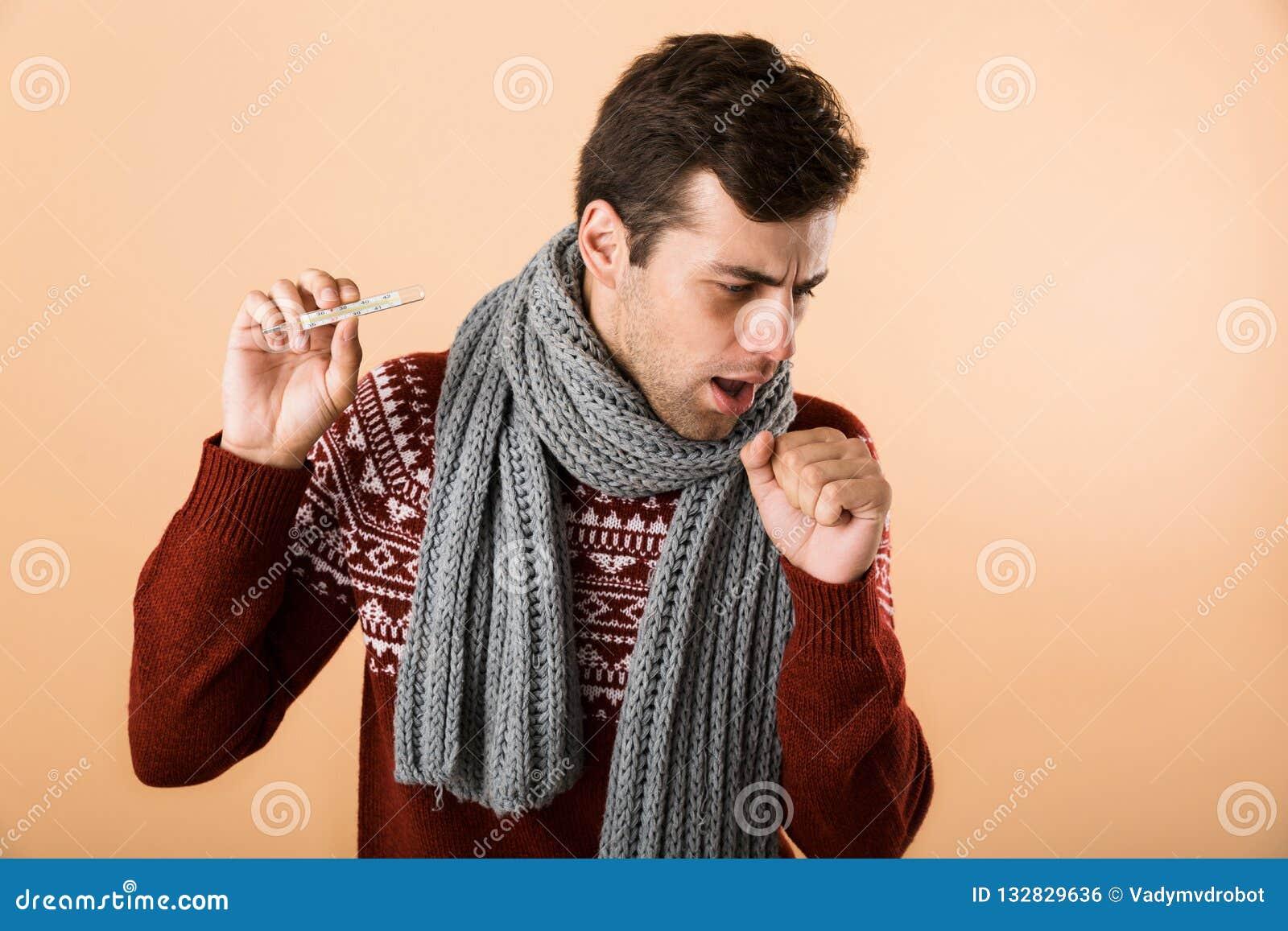 51e7c34a497e Portrait haut étroit d un jeune homme malade triste habillé dans le chandail  et l écharpe d isolement au-dessus du fond beige, thermomètre d apparence,  ...