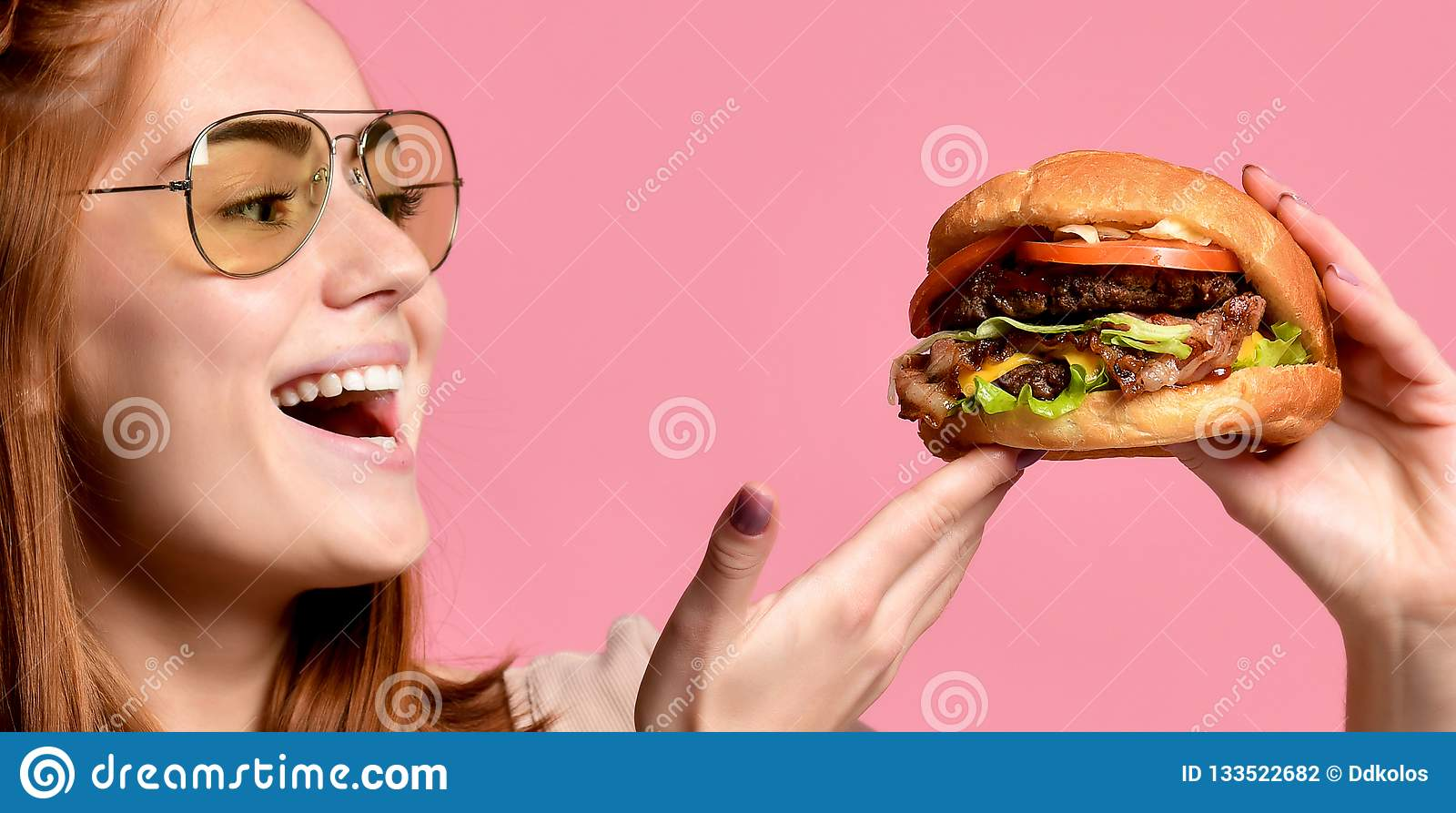 Portrait haut étroit d une jeune femme affamée mangeant l hamburger au-dessus du fond rose