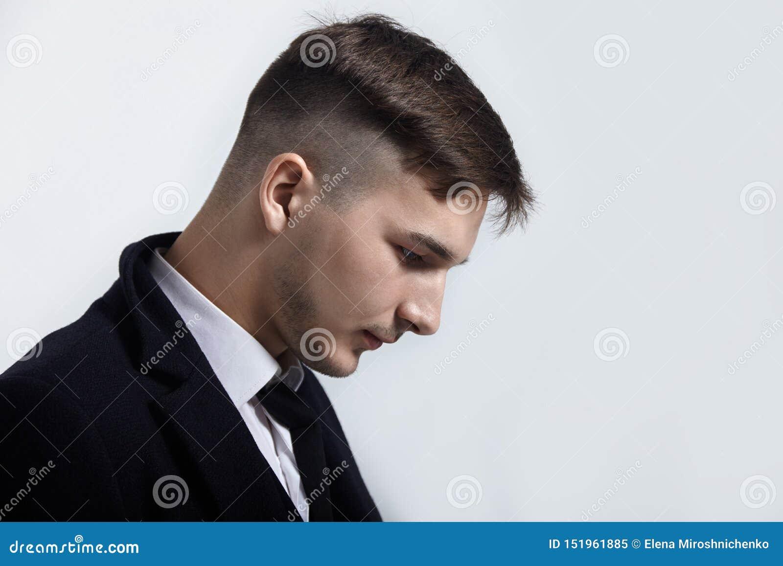 Portrait haut étroit de jeune homme bel sur le fond clair Coiffure à la mode, regard expressif, petite barbe, costume noir classi