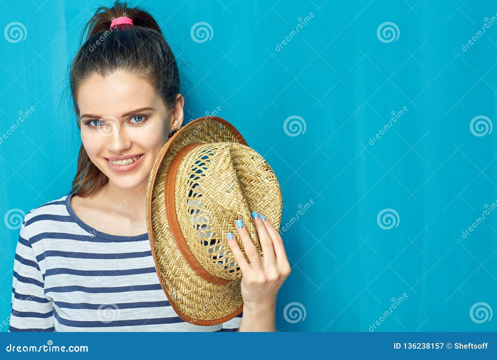 Portrait haut étroit de visage de chapeau de l adolescence de sourire de participation de fille