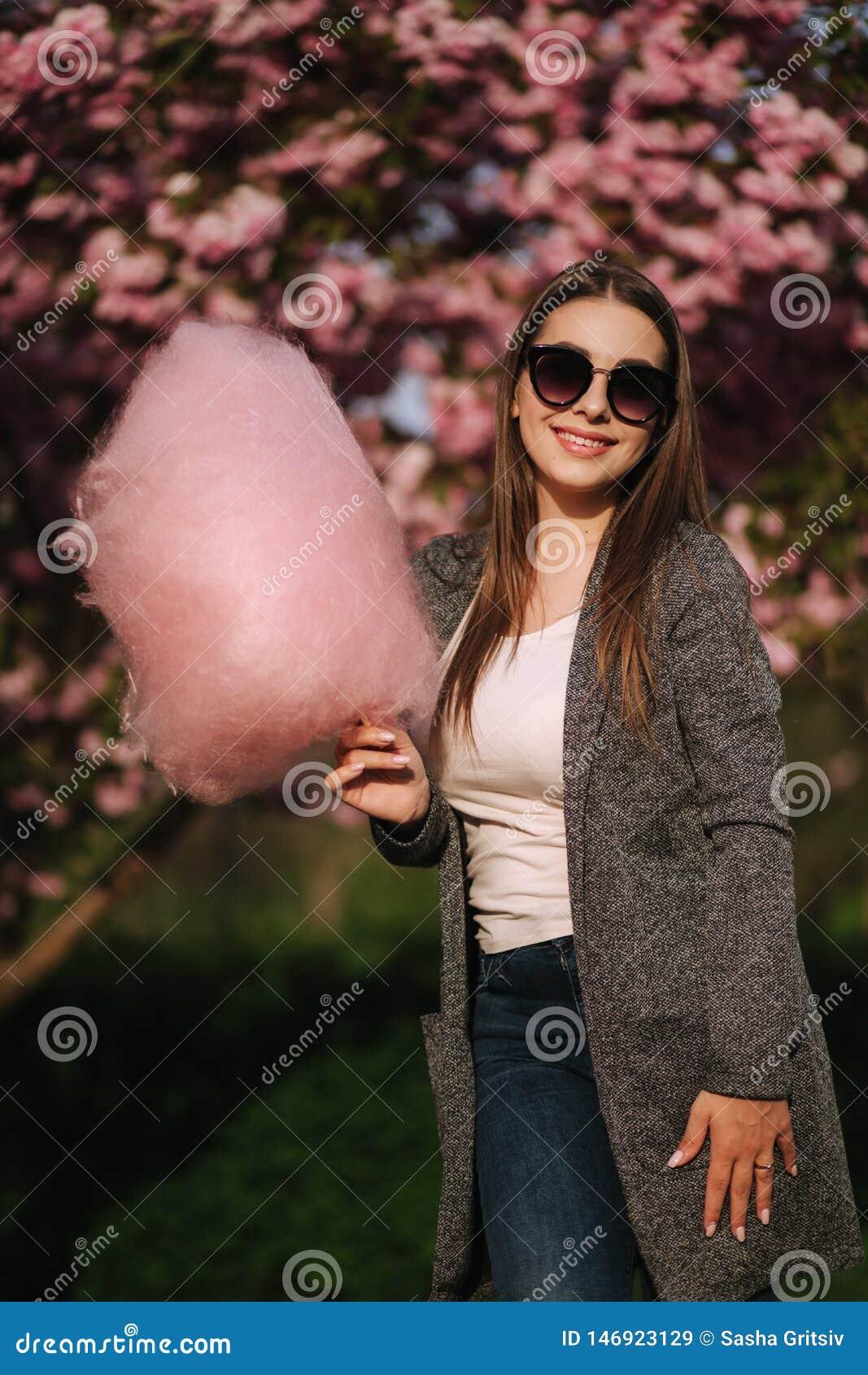 Portrait haut ?troit de fille de sourire tenant la sucrerie de coton dans des mains Fille habill?e dans le blazer et des lunettes
