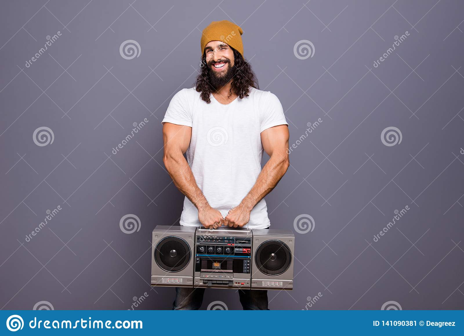 Portrait of his he nice handsome attractive cheerful wavy-haired guy holding in hands retro vintage player loud hit