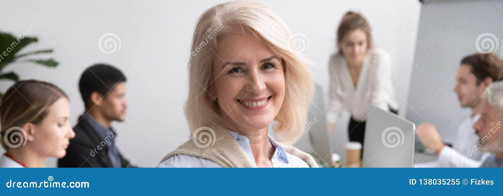 Portrait horizontal de photo de femme d affaires supérieure souriant regardant la caméra