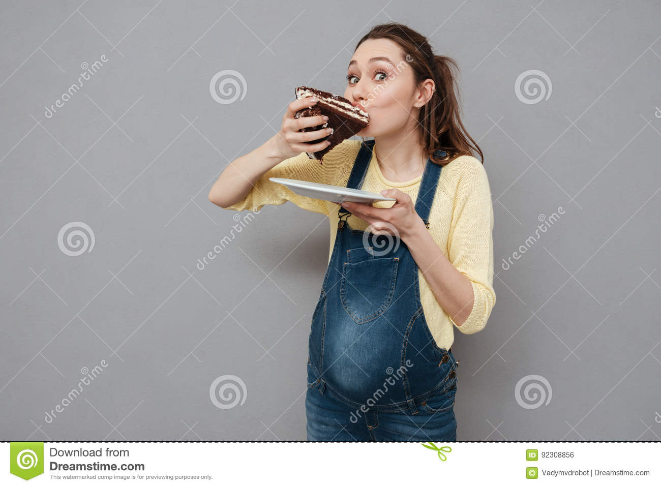 Portrait of a hungry pregnant woman eating sweet chocolate cake