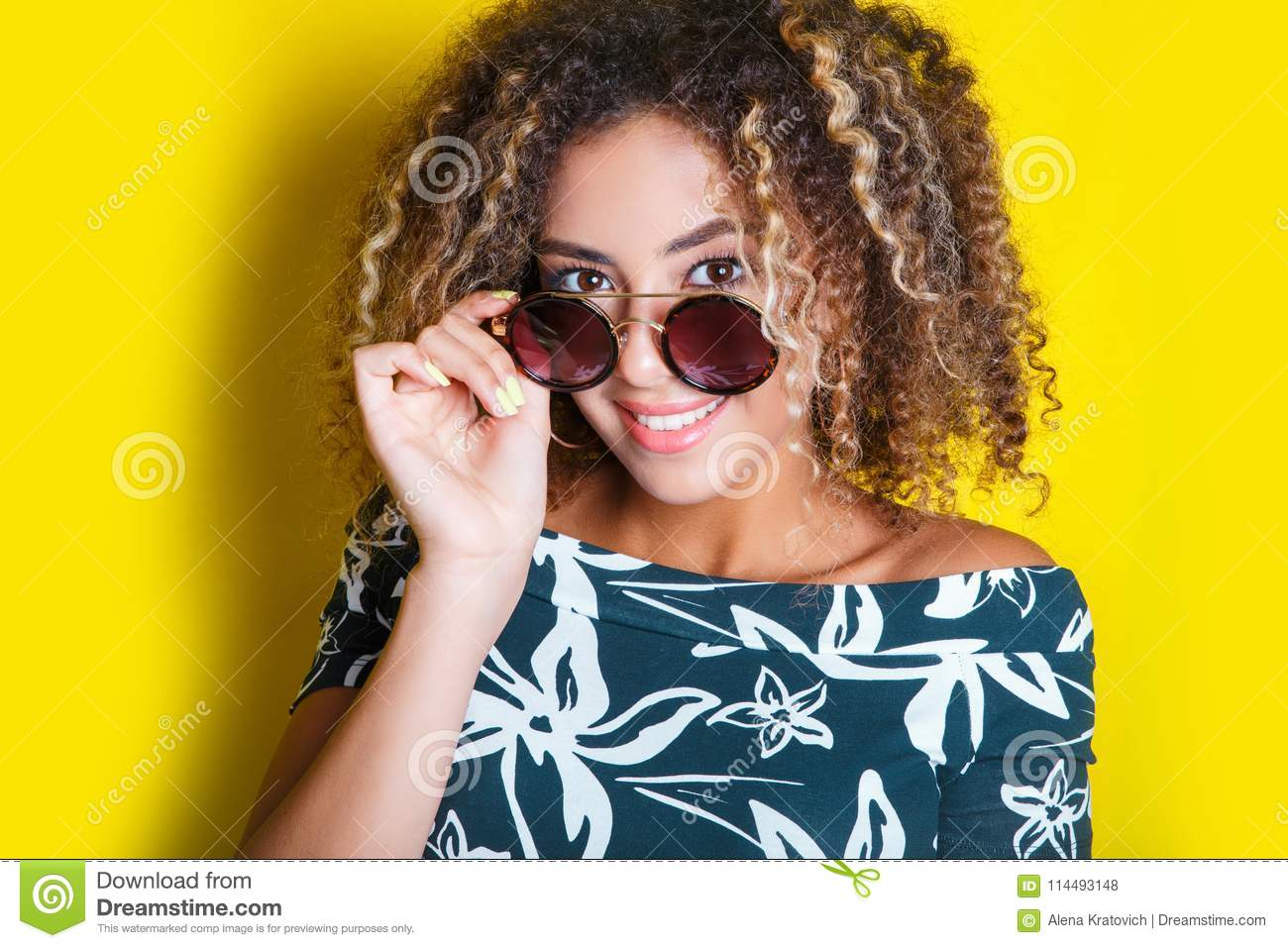 Portrait of a young afro american woman in sunglasses. Yellow background. Lifestyle.