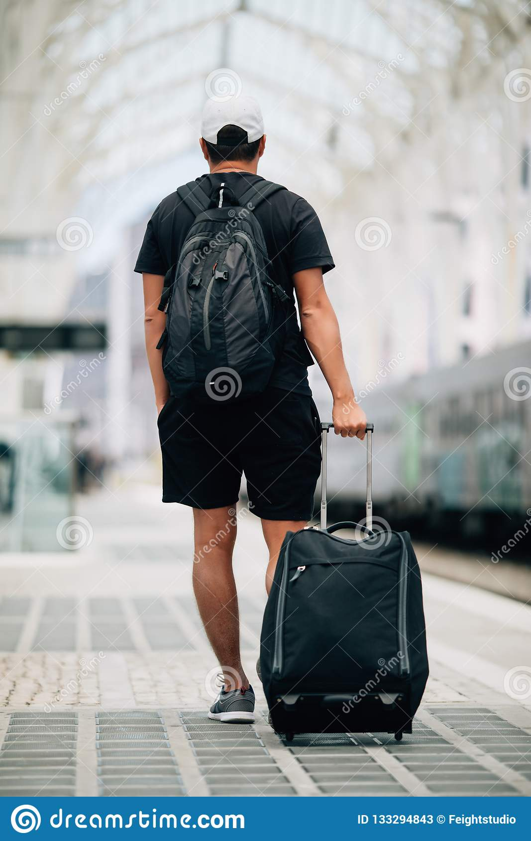 Portrait intégral d un jeune homme heureux marchant avec la valise à la station de train concept de course
