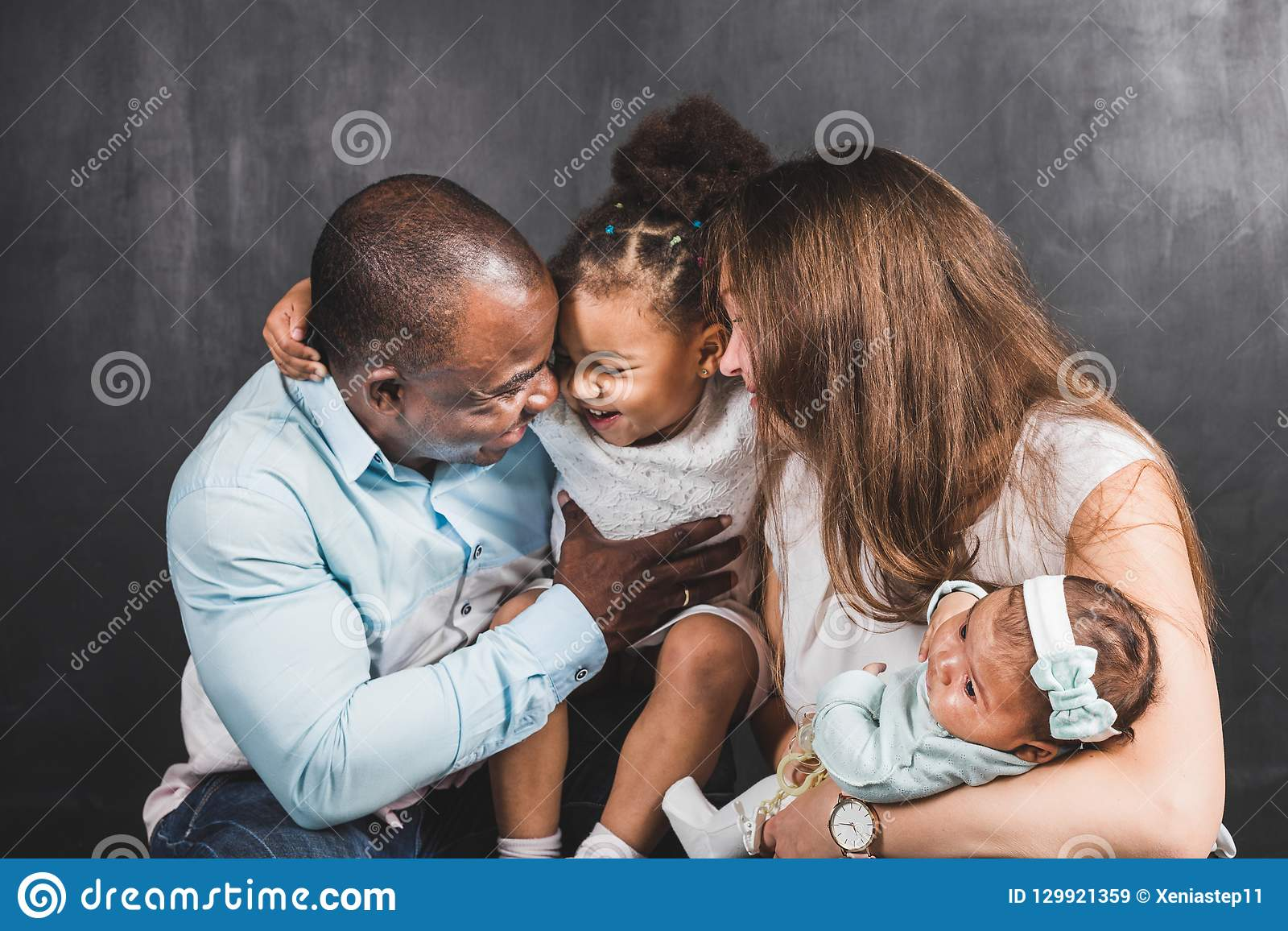 Portrait of an international family with two children on a black wall background