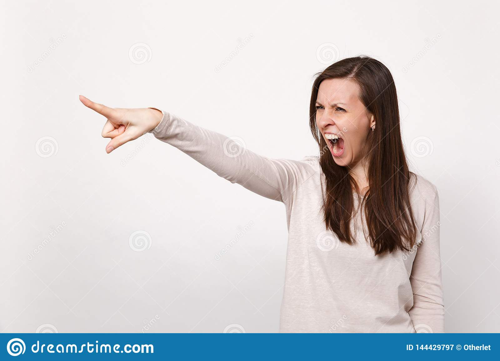 Portrait Of Irritated Screaming Young Woman In Light