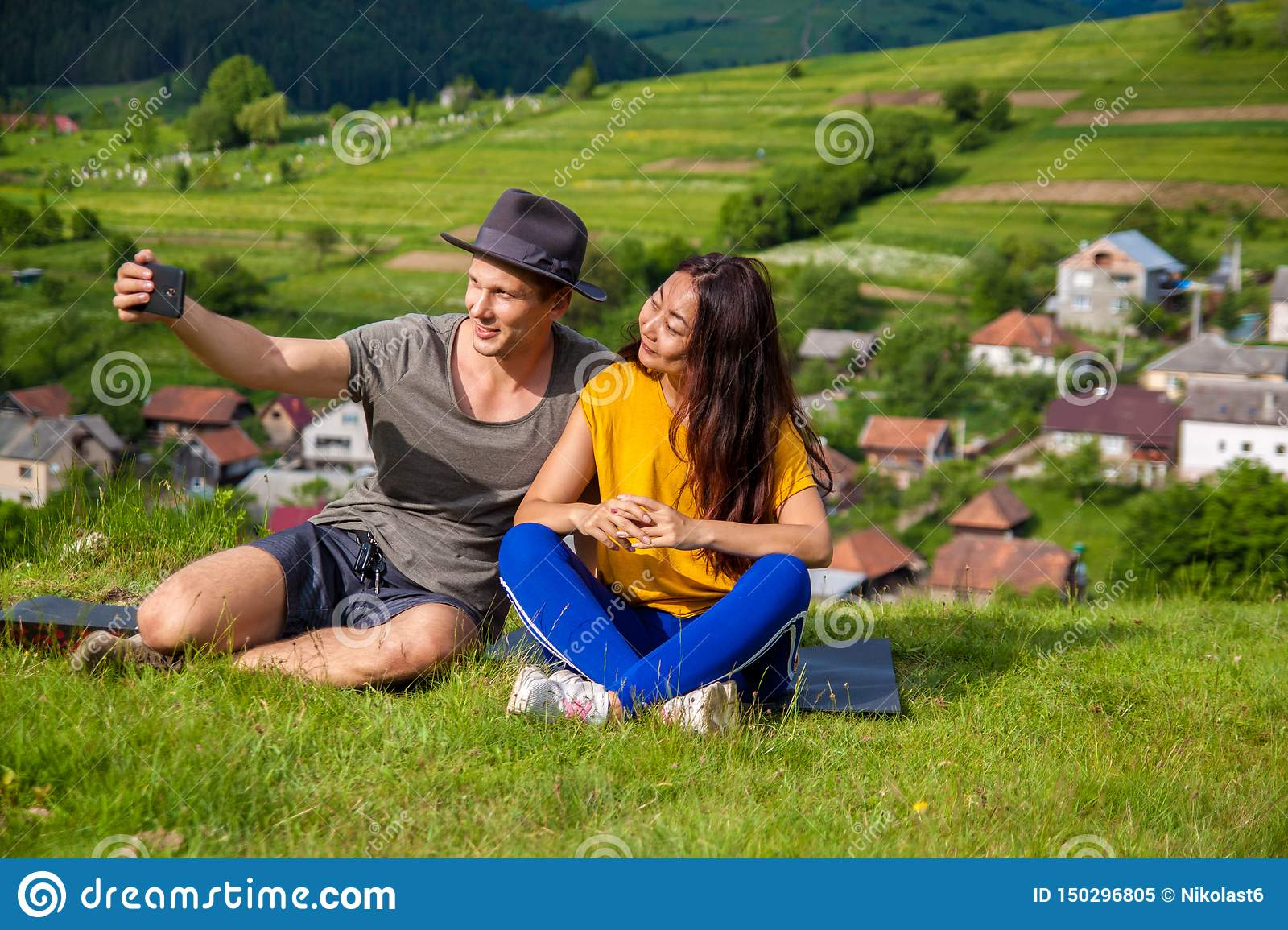 Portrait of joyful girl and boy sitting on the mountain and making selfie.