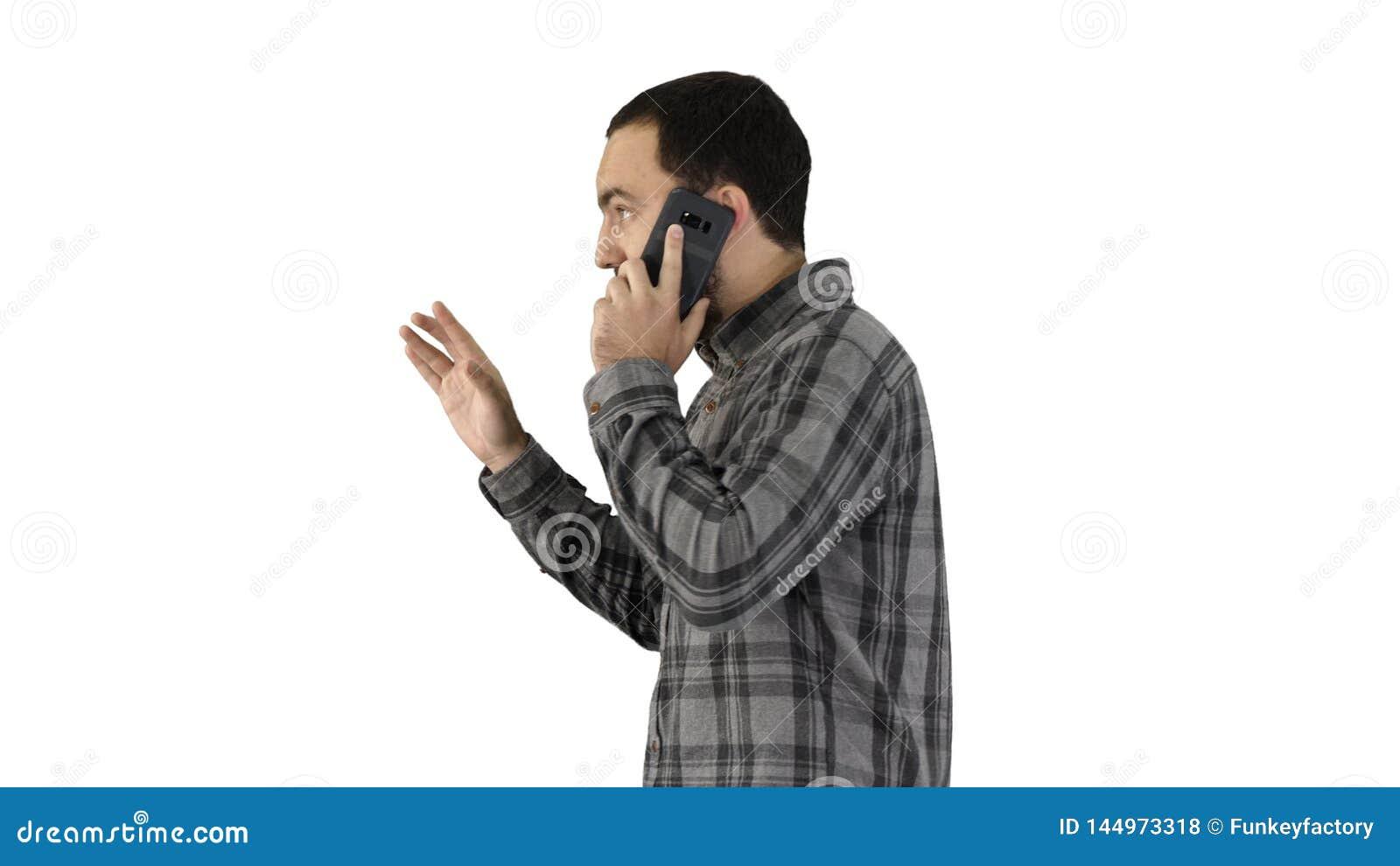 Portrait lat?ral d un ?tudiant heureux marchant et parlant au t?l?phone portable sur le fond blanc