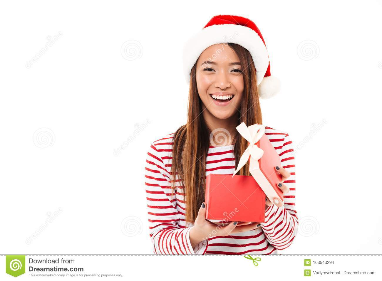 d2e6345609673 Portrait of a laughing asian girl in christmas hat holding opened gift box  and looking at camera isolated over white background