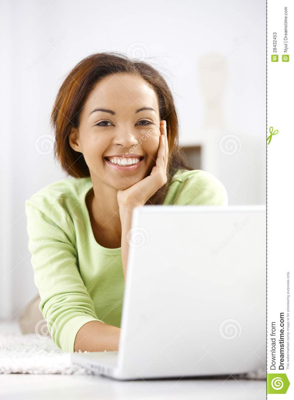 Portrait of laughing ethnic girl with laptop