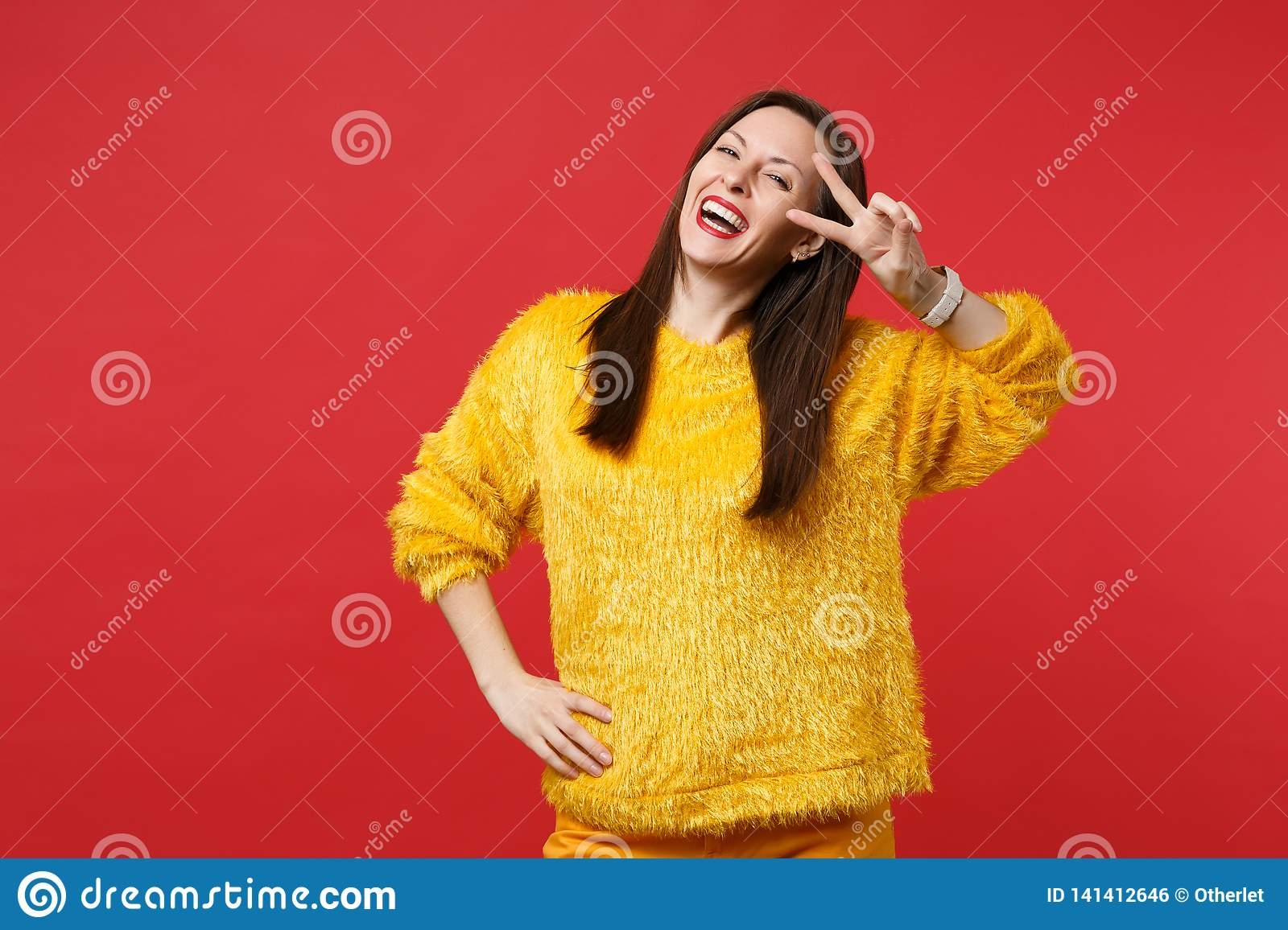 Portrait of laughing funny young woman in yellow fur sweater showing victory sign isolated on bright red wall background