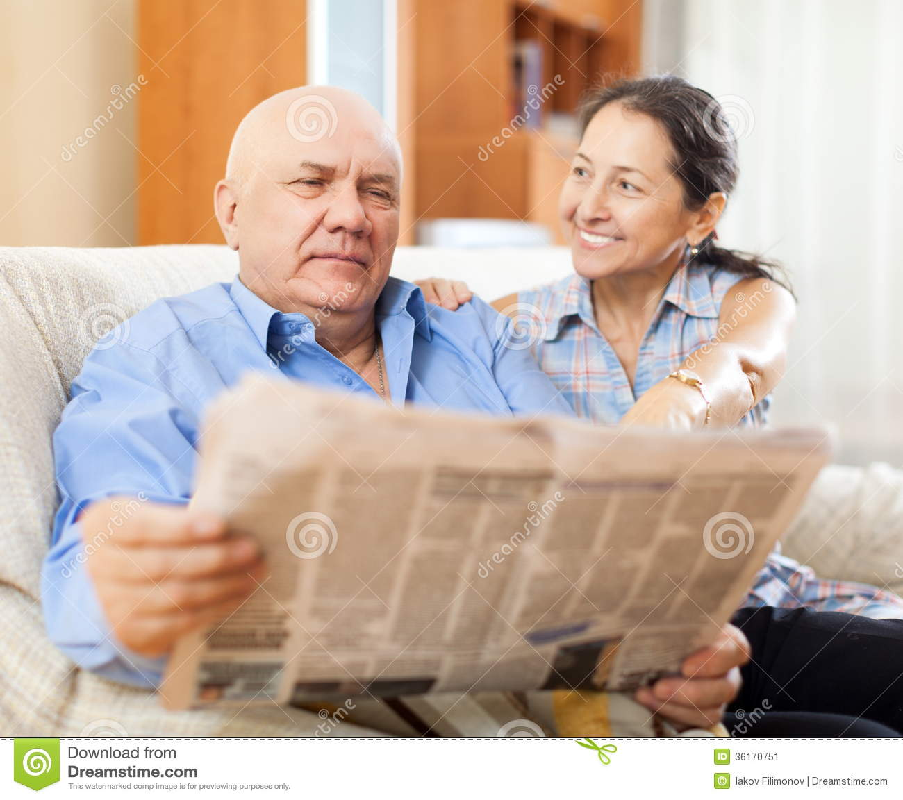 Portrait of laughing mature woman and elderly man with newspaper