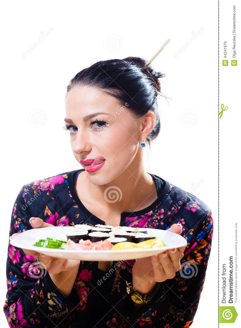 Portrait of licking lips beautiful young woman having fun sitting at the table and holding sushi plate