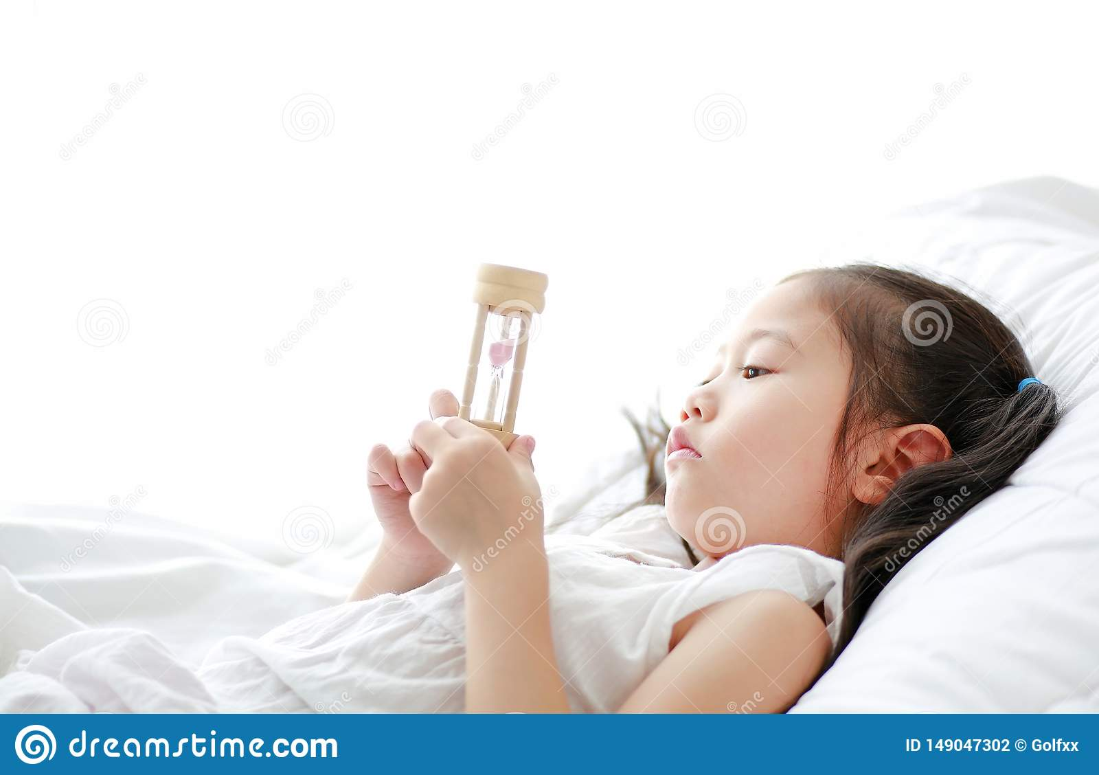 Portrait of little Asian girl looking at hourglass in hand lying on bed at home. Waiting times with sandglass