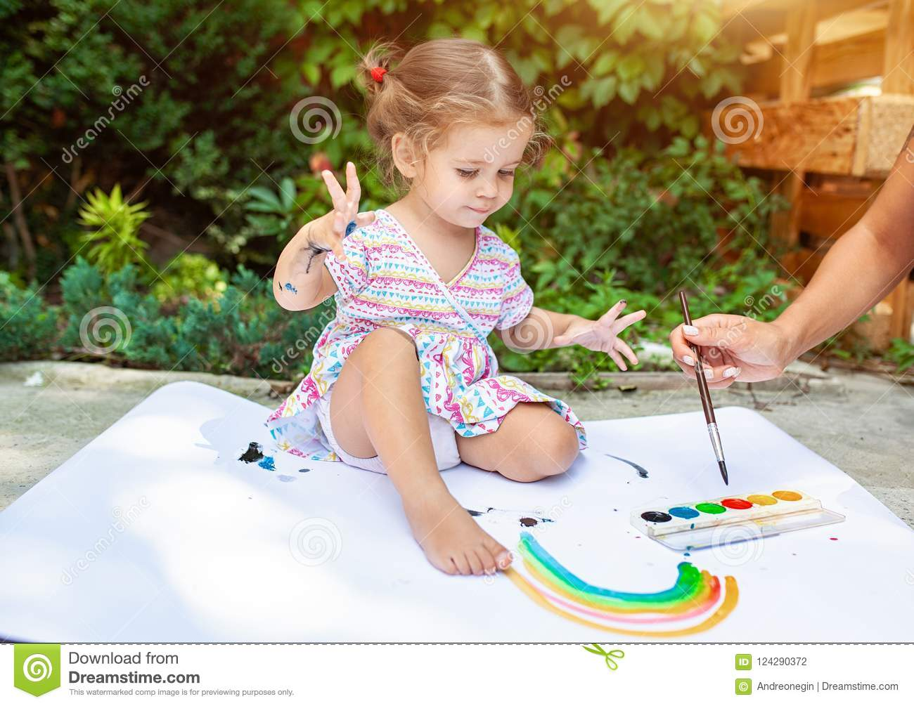 portrait of little blonde girl painting summer outdoor stock photo