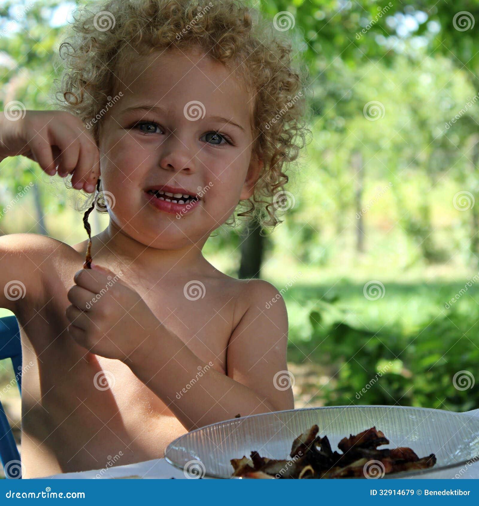 Portrait of a little boy eating in the garden