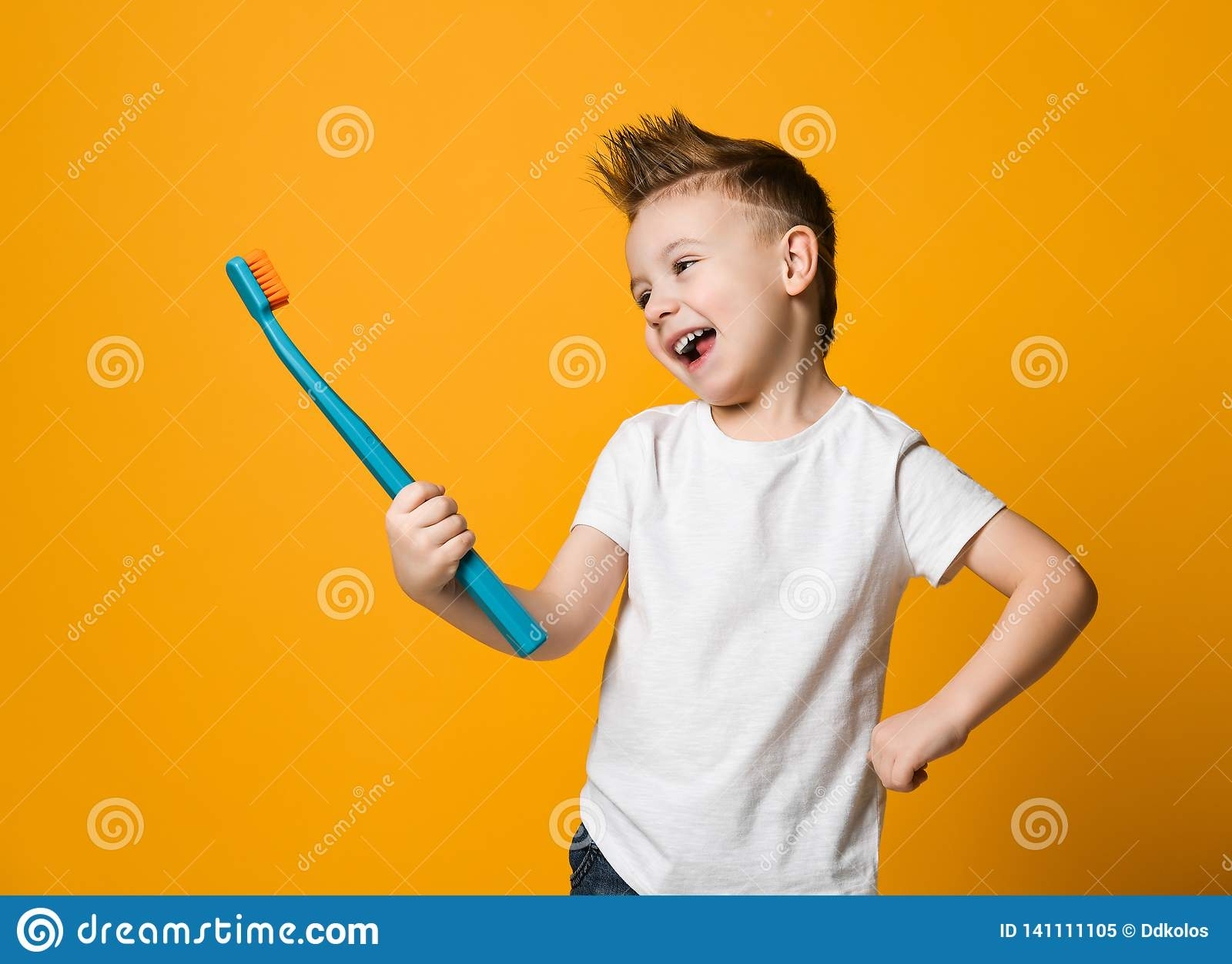 Portrait of a little boy holding a tooth brush over yellow background