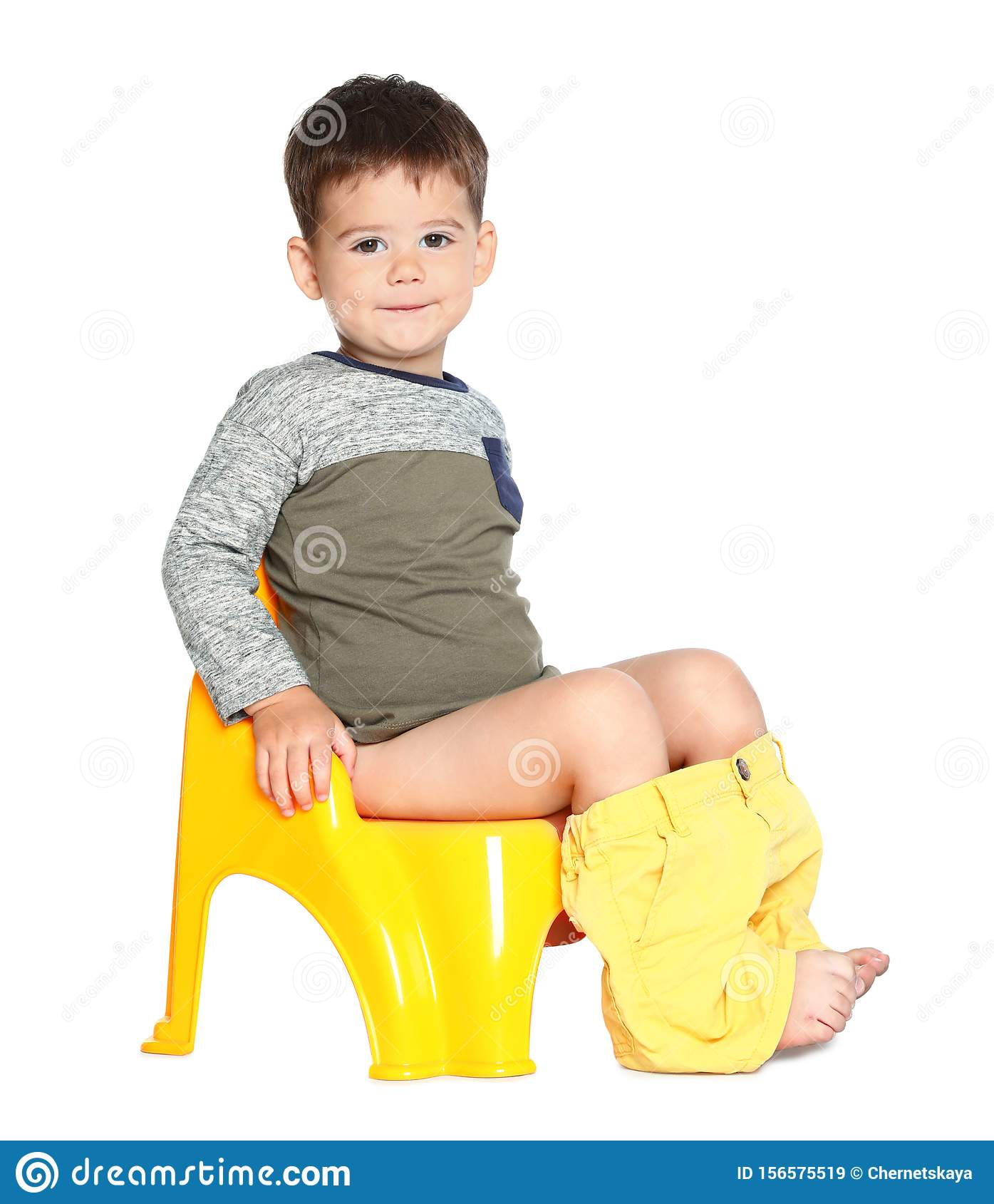 Little Blond Boy Sitting On High Chair In Cafe With