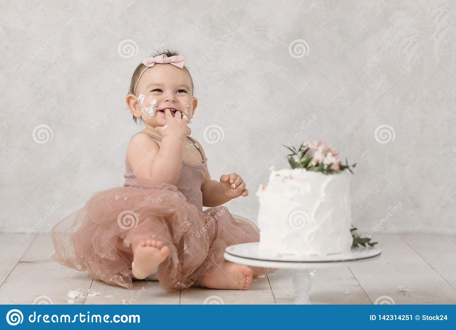 Portrait of a little cheerful birthday girl with the first cake. Eating the first cake. Smash cake