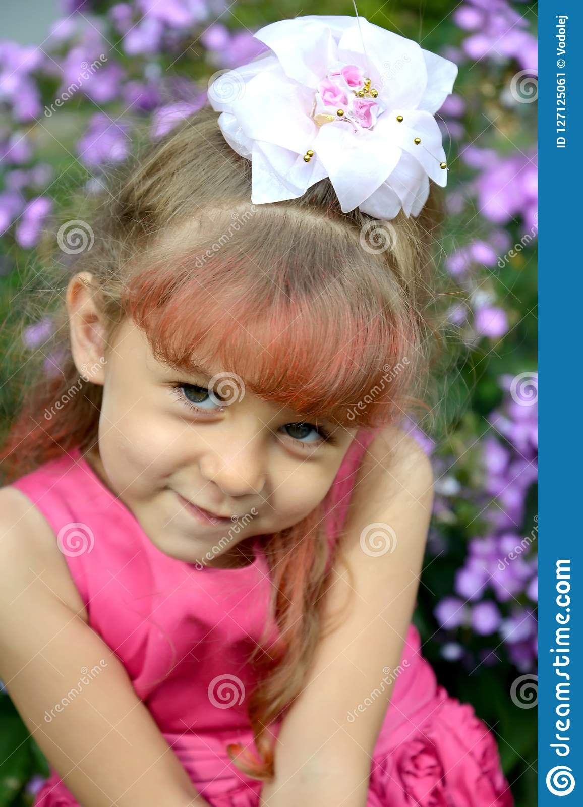 Portrait of the little coquettish girl in a garden