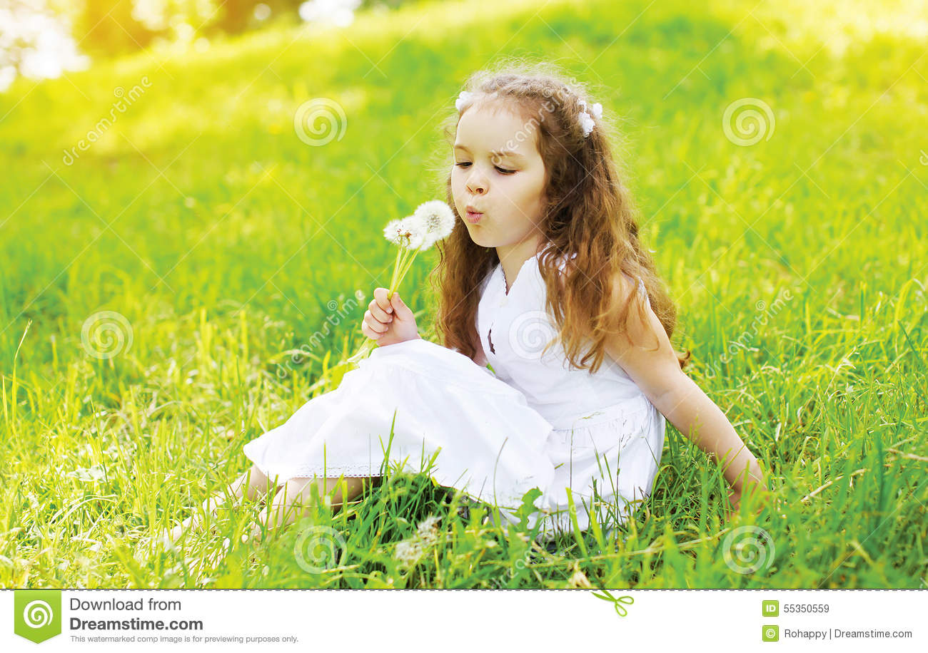Portrait Of Little Girl Child On The Grass Blowing White Flowers