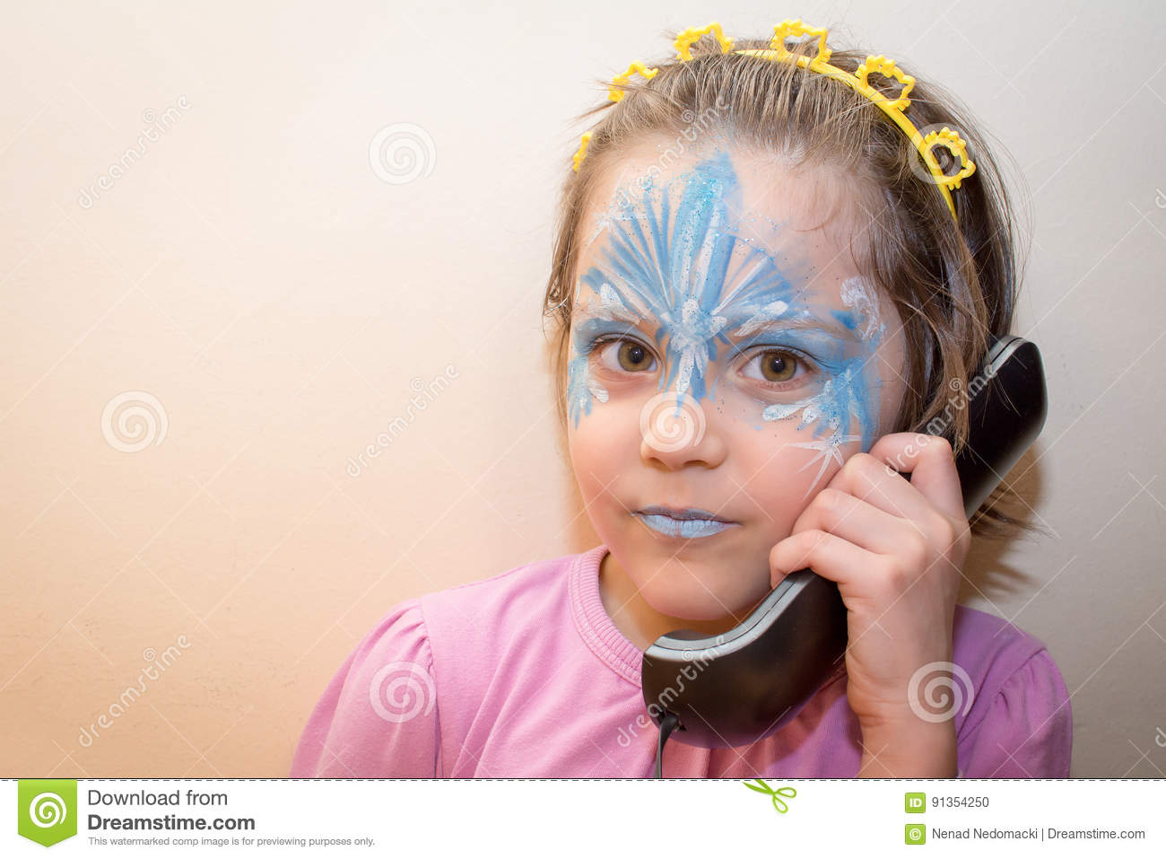 Portrait Of Little Girl With Face Painting Talking On The Old Phone