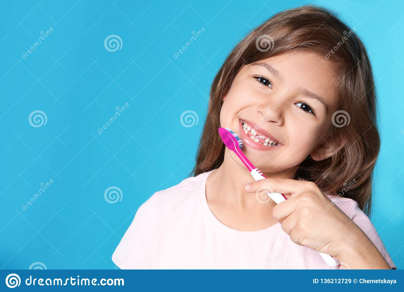 Portrait of little girl with toothbrush on color background.