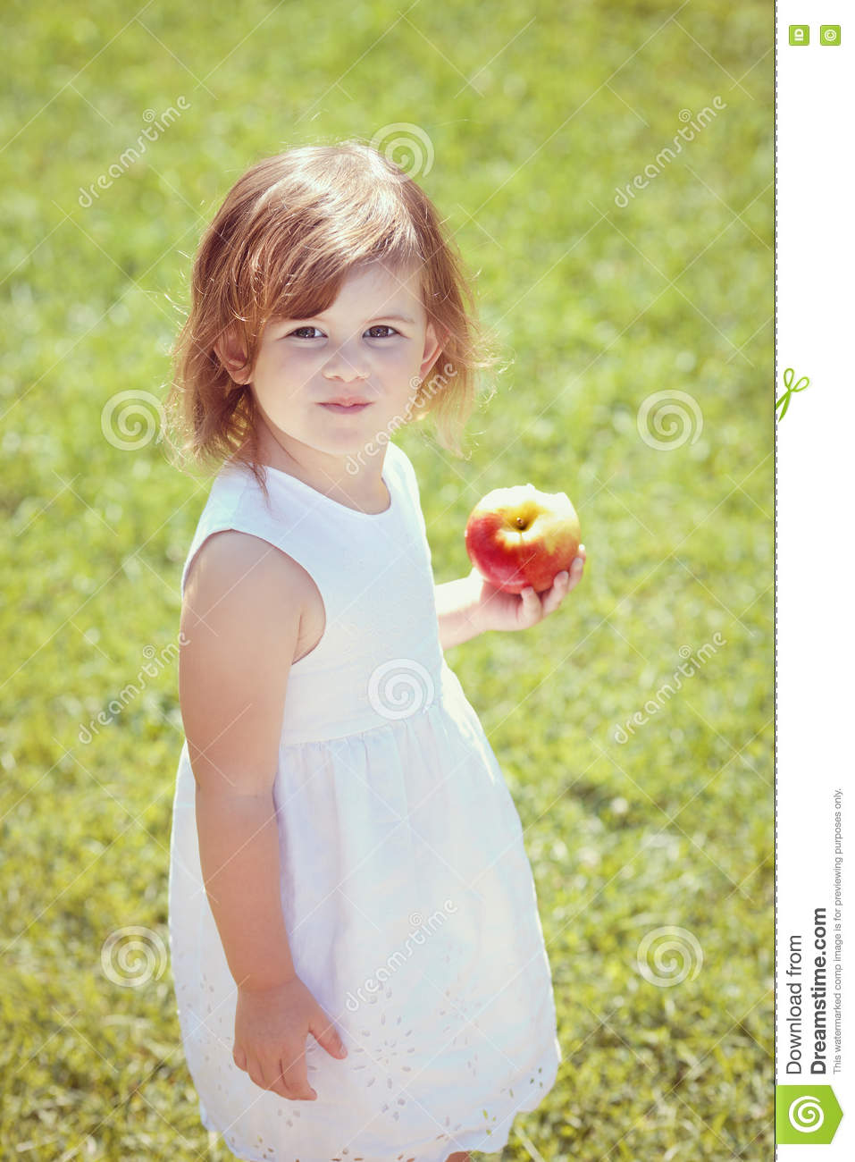 ad7481e43e0 Closeup portrait of a adorable funny toddler child girl holding eating apple  in park outside on summer day