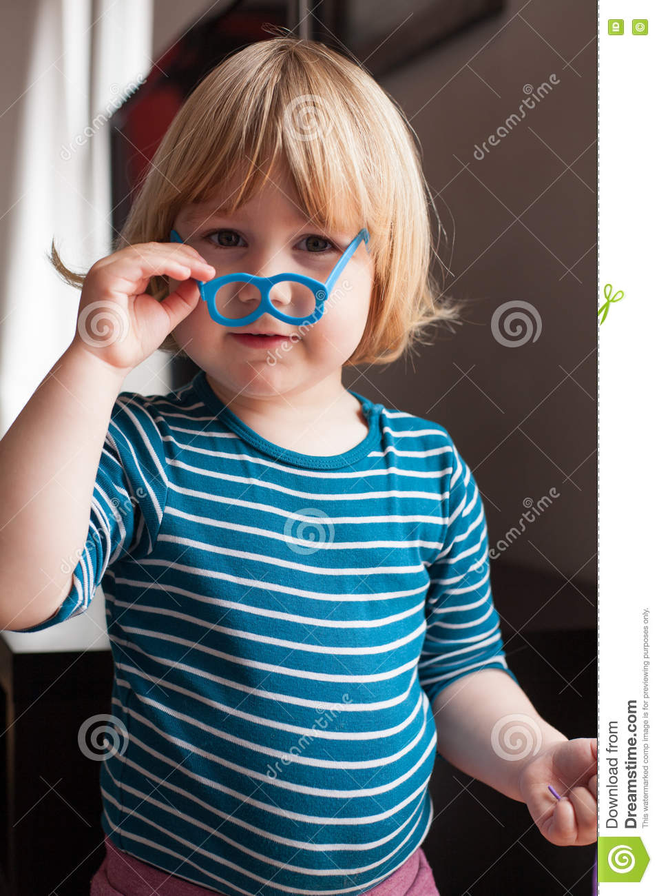 5c989e1f8a73 Funny portrait of blonde two years old child with striped blue and white  sweater inside home playing holding with hand little plastic toy glasses in  face ...