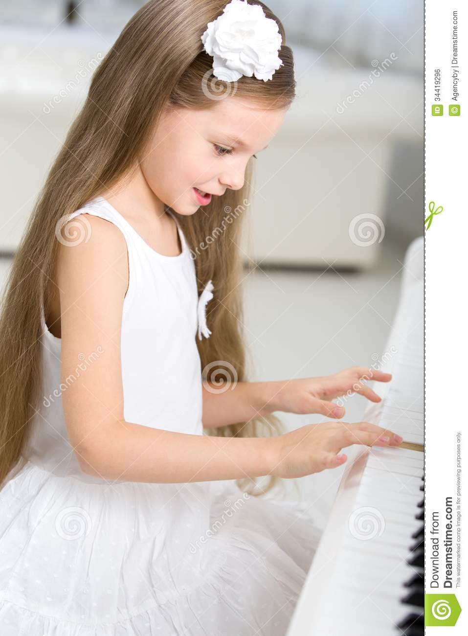 Portrait of little musician in white dress playing piano royalty free