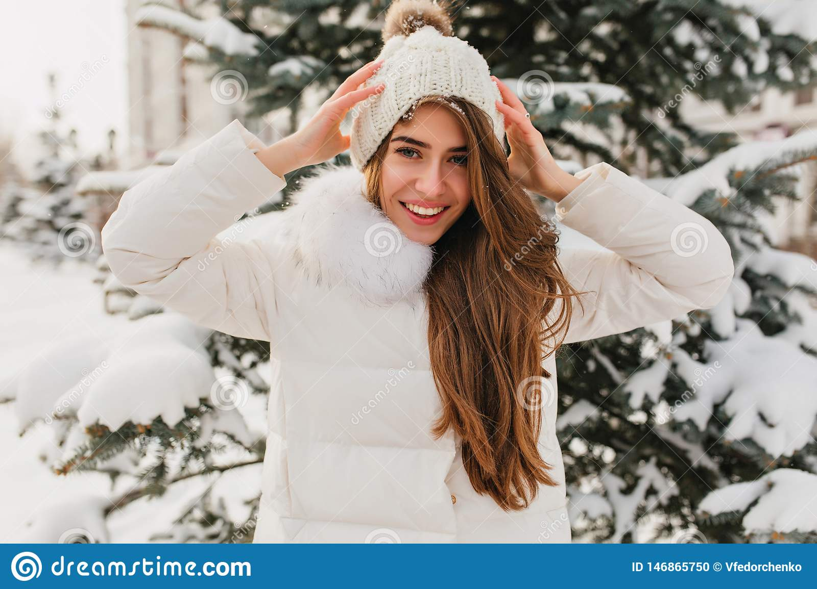 Portrait lovely girl with long light-brown hair showing true happy emotions in winter day on fir tree background