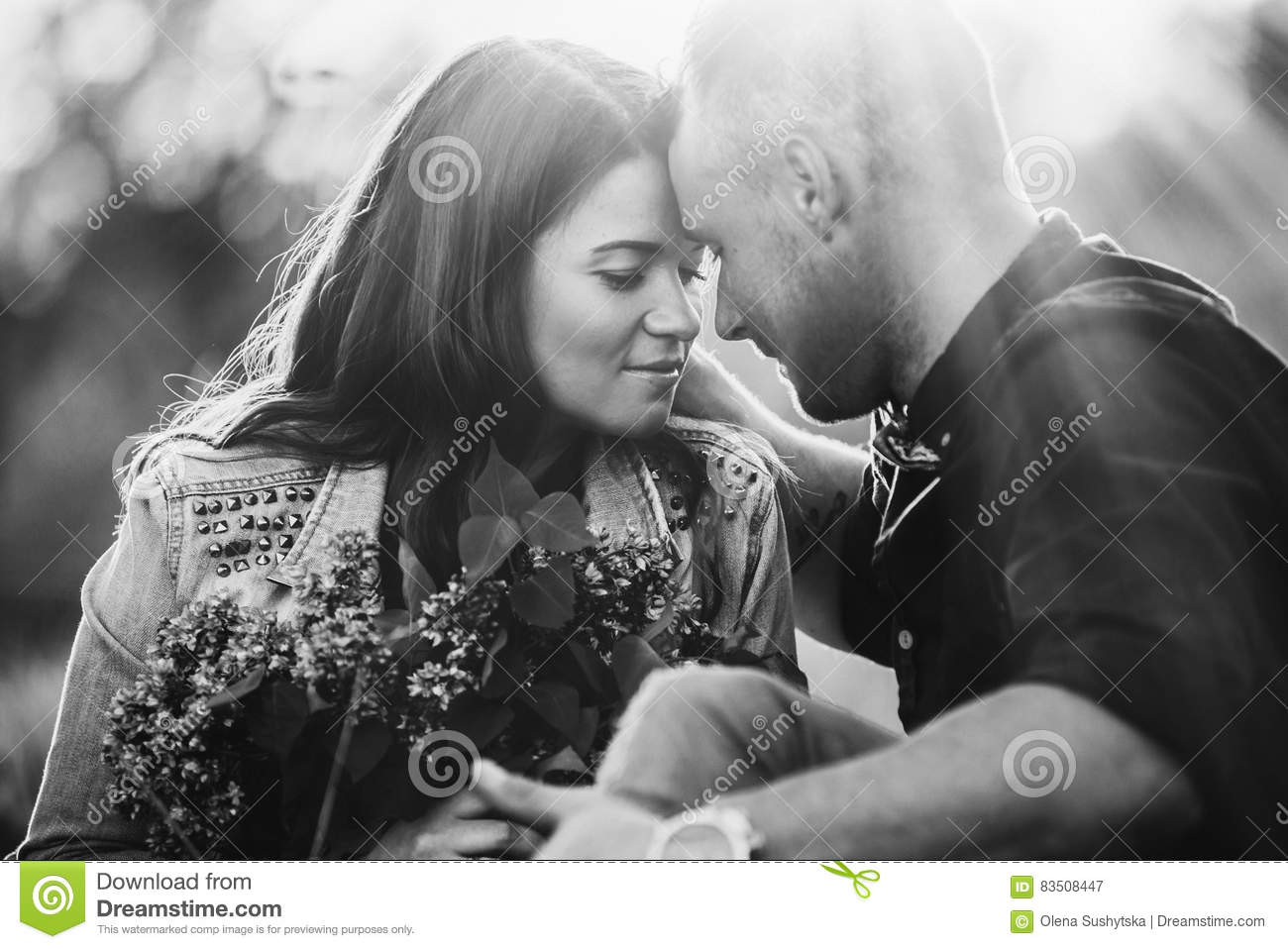 Young couple on holiday being romantic and kissing while relaxing during a summer break vacation love and relationships outdoors black and white