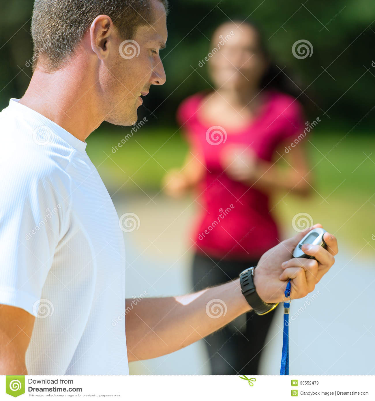 Portrait of male coach timing runner
