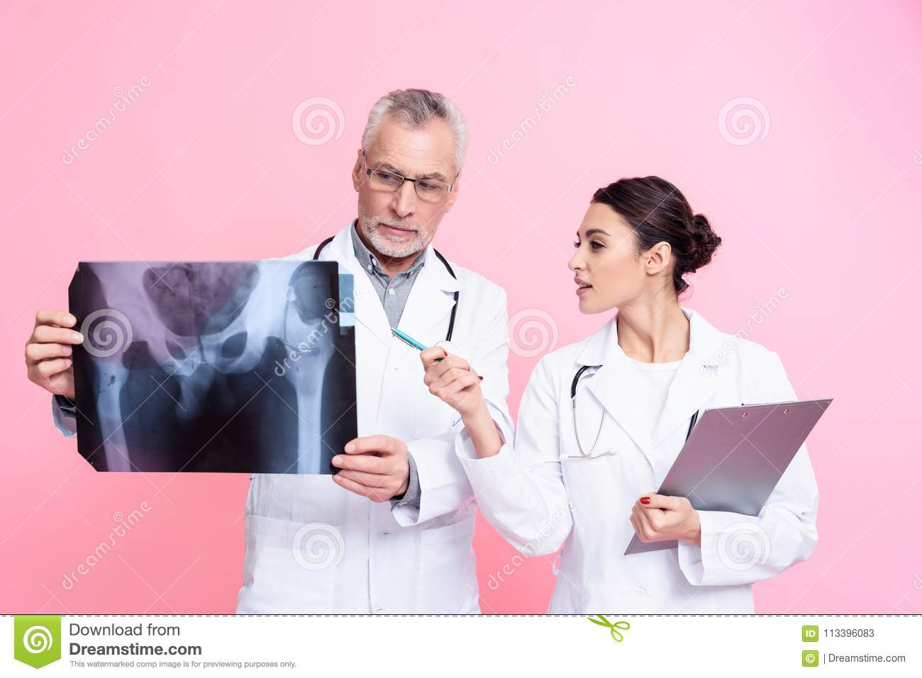 Portrait of male and female doctors with stethoscopes holding x-ray and clipboard isolated.