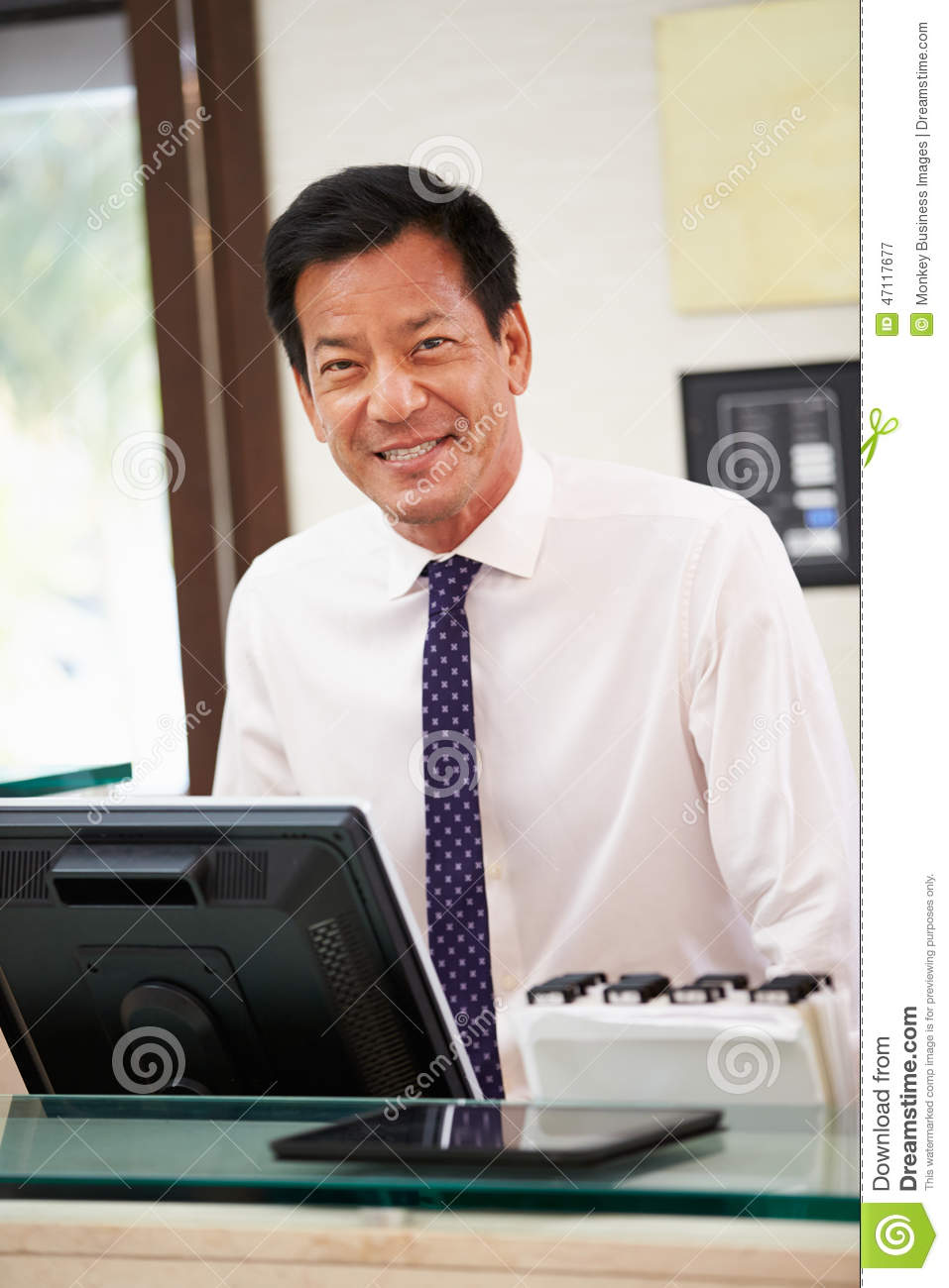portrait of male receptionist at hotel front desk stock photo portrait of male receptionist at hotel front desk