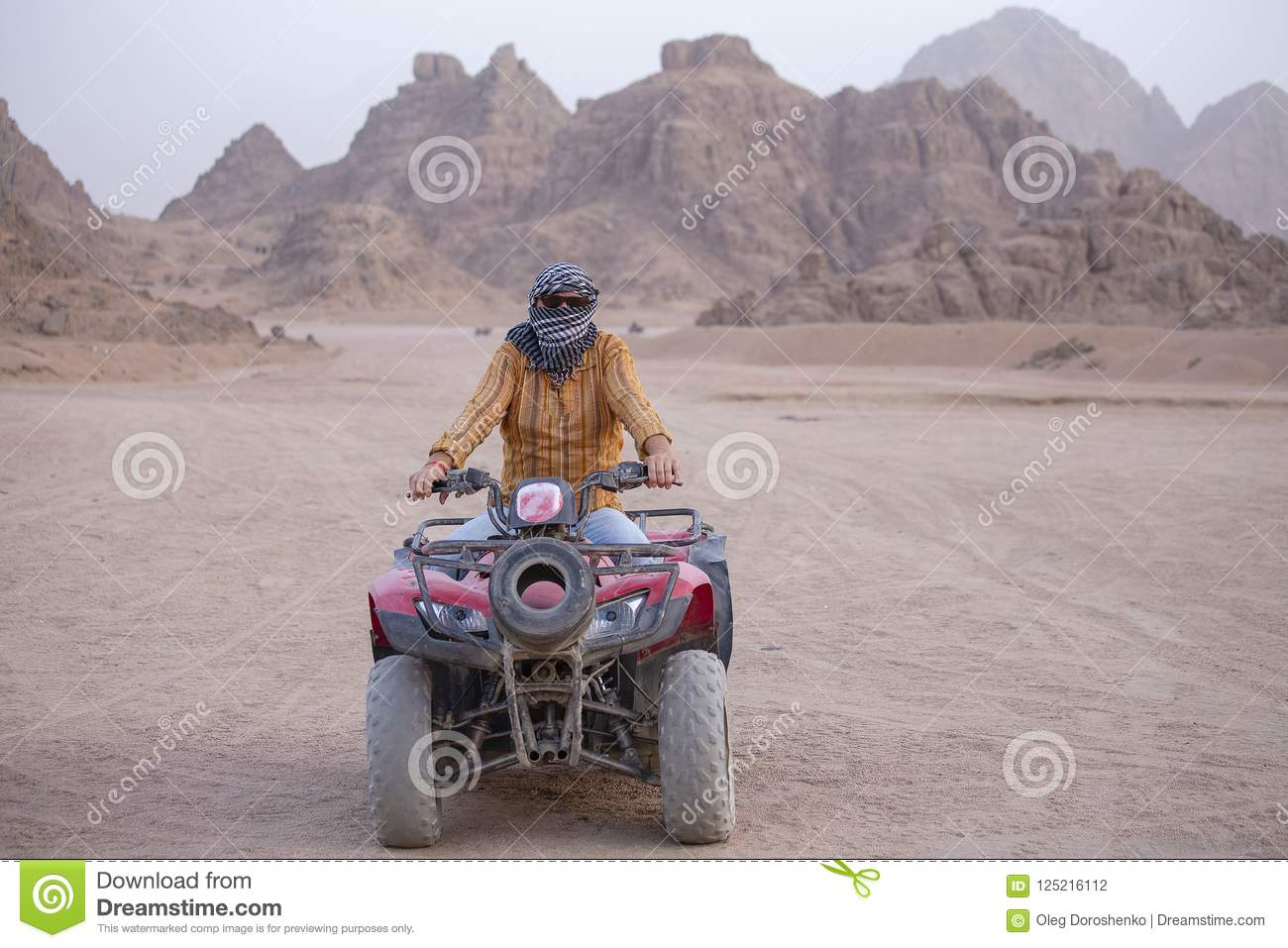 Portrait of a man on an ATV. Quad bikes safari in desert near Sharm El Sheikh, Egypt