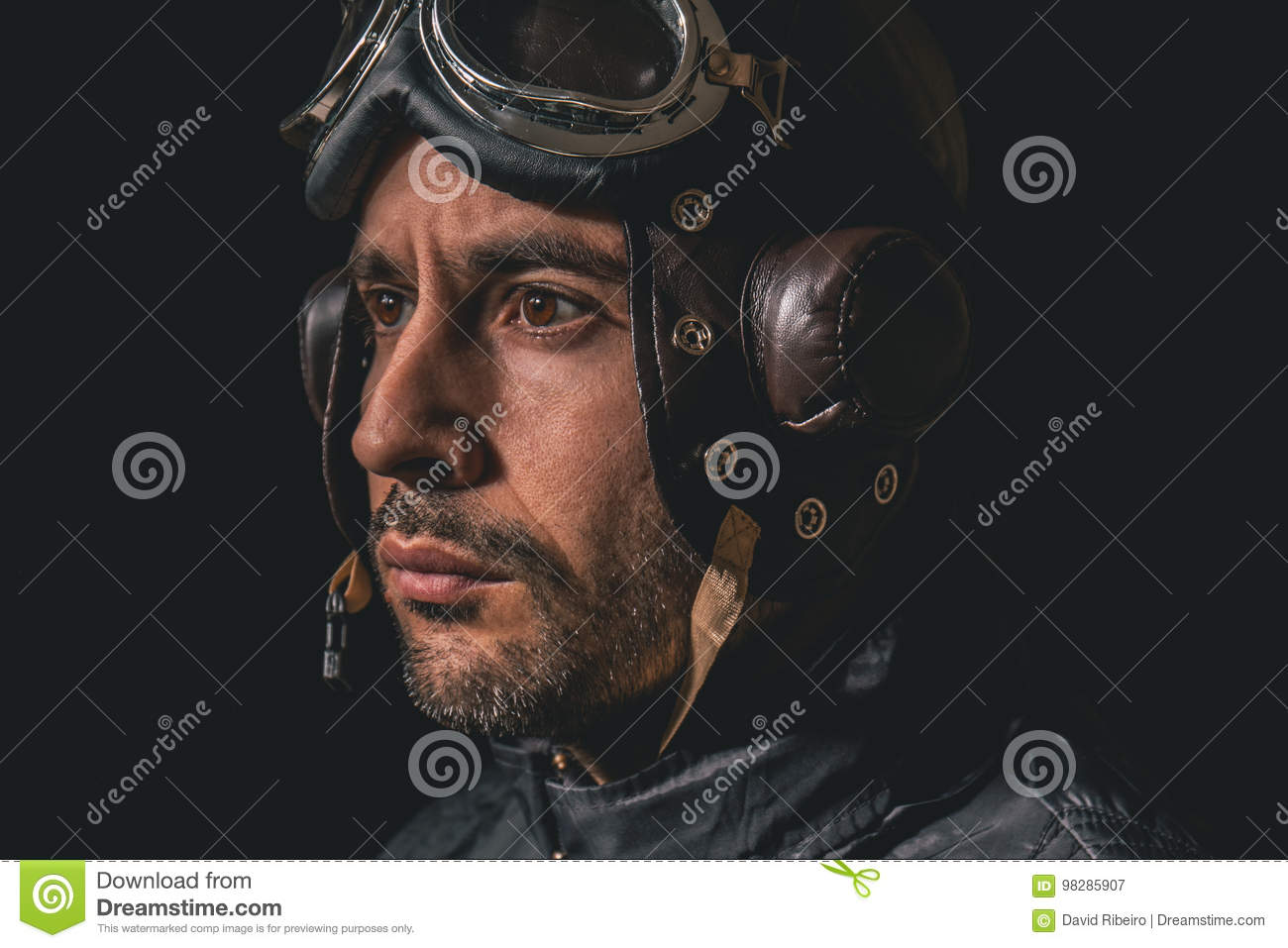 Portrait of a man with aviator helmet and goggles looking away to the distance