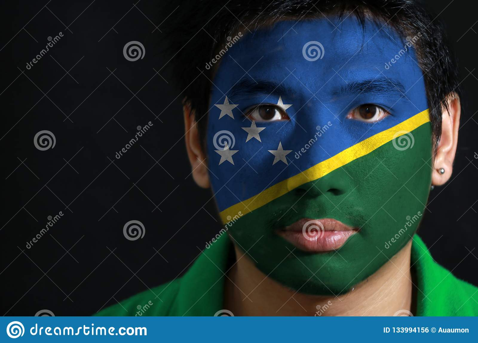 Portrait of a man with the flag of the Solomon Islands painted on his face on black background.