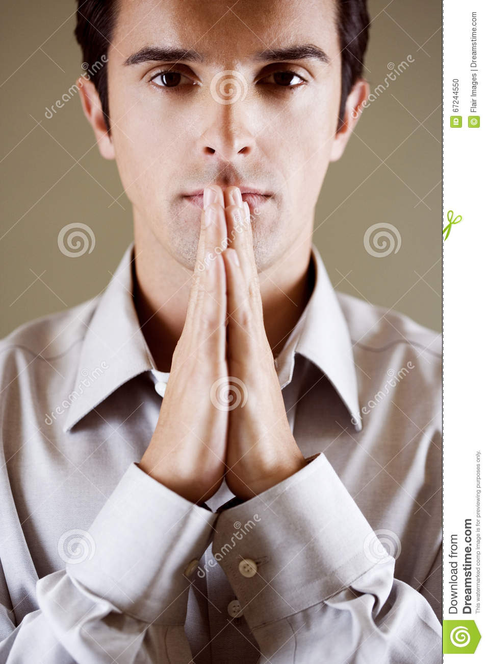 Portrait of a man with his hands in a praying position